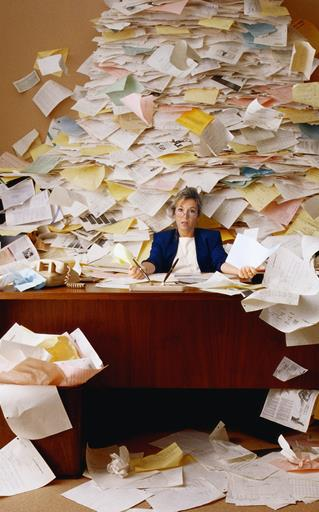 woman at paper clutter desk